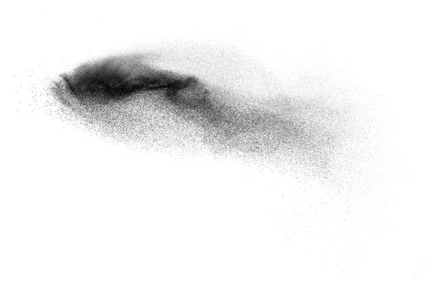 Le particelle nere schizzano su sfondo bianco. polvere di polvere nera che esplode.