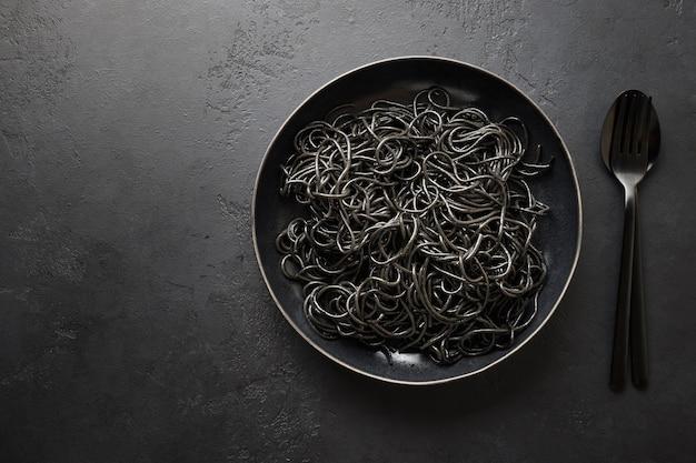 Spaghetti di pasta nera al nero di seppia su fondo nero