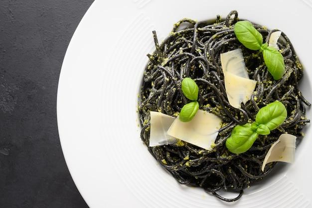 Spaghetti di pasta nera al nero di seppia con salsa pesto in ciotola nera su fondo nero.
