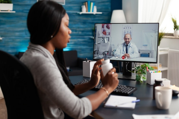 Paziente nero che discute il trattamento delle pillole con il medico durante la riunione di videochiamata online