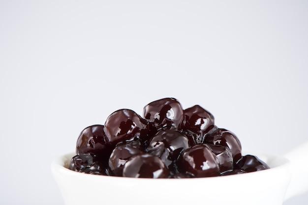 Perle nere. perle di tapioca bollite per bubble tea su sfondo bianco. copia spazio