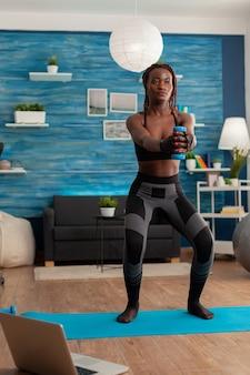 La persona di colore si è concentrata facendo squat usando manubri con le braccia tese, con i piedi sul tappetino da yoga nel soggiorno di casa per la forza muscolare dopo l'allenamento online per uno stile di vita sano.