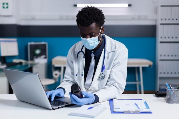 Persona di colore con professione medica che utilizza laptop