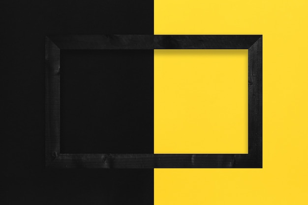 Cornice per foto nera posizionata su sfondo di carta gialla e nera e con spazio per la copia.