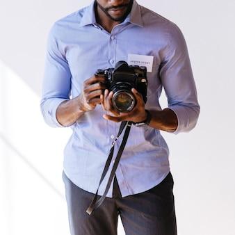 Fotografo nero che utilizza un modello sociale di fotocamera a pellicola retrò