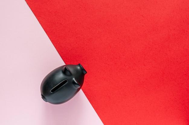 Salvadanaio nero su un tavolo rosa e rosso. concetto di risparmio di denaro