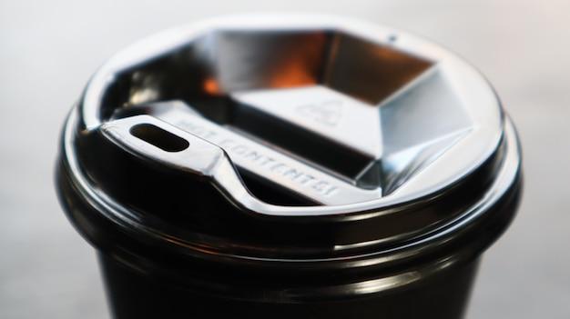Coperchio per tazza da caffè in plastica nera, vista dall'alto. tazza di caffè da asporto sfondo nero. primo piano della tazza monouso su un tavolo di legno. stile minimalista.