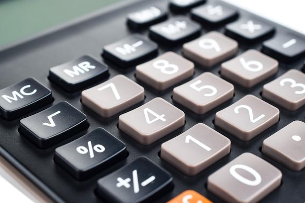 Calcolatrice digitale in plastica nera, isolata su uno sfondo bianco, primo piano. economia dei simboli, matematica, contabilità, concetto di finanza. il giorno della conoscenza, per calcolare, per contare i soldi.