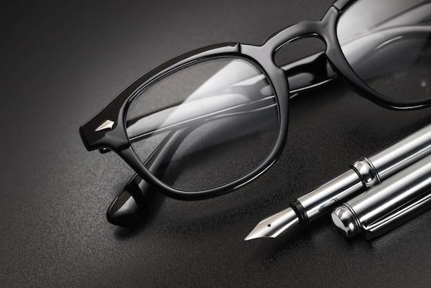 Occhiali da vista in plastica nera per la correzione della vista con penna stilografica su sfondo scuro
