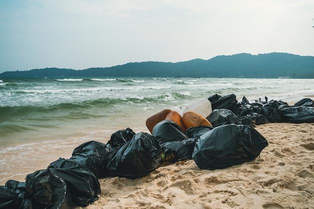 Sacchi di immondizia di plastica neri pieni di spazzatura sulla spiaggia. raccolta rifiuti, pulizia della natura, raccolta rifiuti in spiaggia.