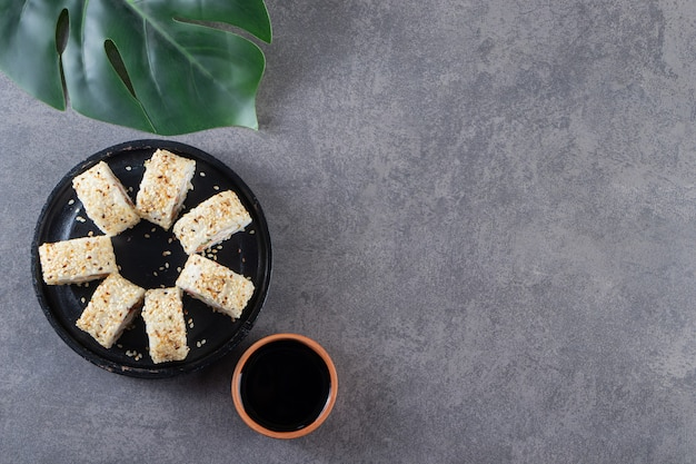Piatto nero di deliziosi rotoli di sushi con semi di sesamo sulla superficie della pietra