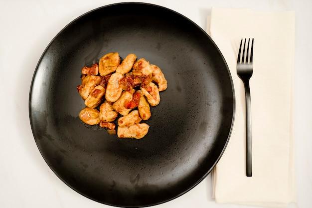 Piatto nero di gnocchi con salsa rossa su un tavolo di marmo bianco. accompagna una moderna forchetta nera. cibo italiano