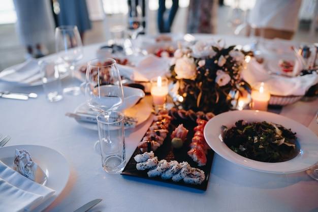 Piatto nero per servire sushi e panini su una tovaglia bianca sul tavolo con insalata in un piatto a