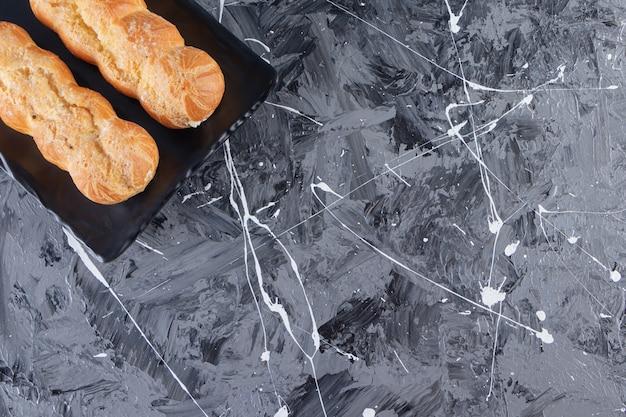 Piatto nero di bignè dolci sul tavolo di marmo.