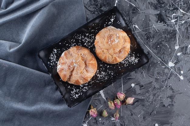 Piatto nero di profiteroles dolci con panna montata sul tavolo di marmo.