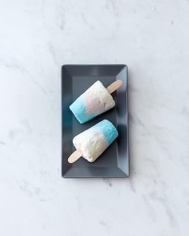 In un piatto nero, due gelati sani fatti in casa su un tavolo di marmo grigio con una copia dello spazio. dessert freddo. lay piatto