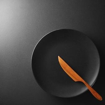 Piatto nero con coltello su uno sfondo nero strutturato.
