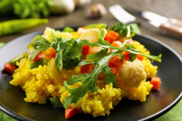 Piatto nero con risotto alle verdure sul tavolo di legno servito