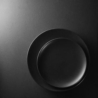 Piatti neri su uno sfondo nero strutturato.