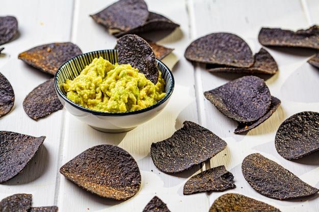 Patatine nere con salsa di avocado - guacamole, sfondo bianco, vista dall'alto. concetto di cibo vegano.