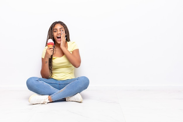 Bella donna nera seduta sul pavimento