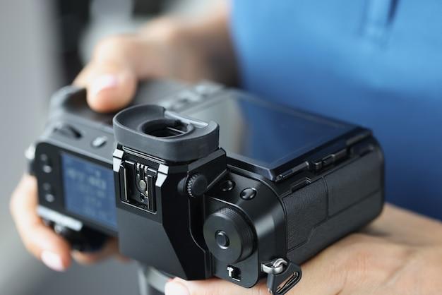 Macchina fotografica professionale nera in primo piano delle mani femminili