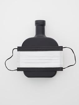 Maschera protettiva nera con rum in bottiglia su sfondo bianco.