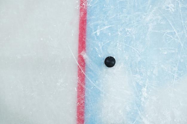 Disco nero sdraiato sulla linea rossa sulla pista di pattinaggio per giocare a hockey su stadio che può essere utilizzato come sfondo per pubblicità o annunci sportivi