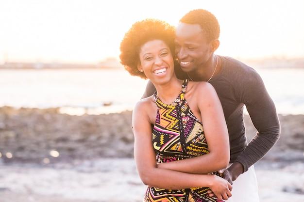 Coppia afroamericana africana di razza nera in relazione o associazione o amicizia che tocca e si gode il tramonto sulla spiaggia nel tempo libero all'aperto di vacanza