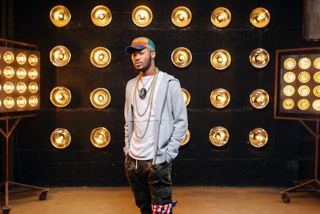Rapper nero in berretto sul palco con faretti