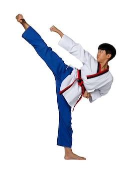 Cintura rossa nera taekwondo karate kid adolescente atleta mostra tradizionale combattimento pose calcio alto in abito uniforme sportiva, ragazzo di 15 anni, studio illuminazione sfondo bianco isolato profilo a figura intera