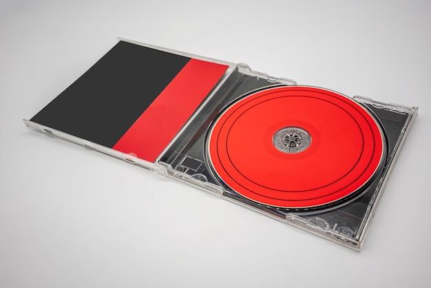 Compact disc nero e rosso, cd, con custodia in plastica isolata sulla superficie bianca.