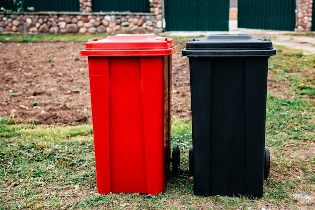 Contenitori per rifiuti neri e rossi per la separazione e lo smistamento vetro, plastica, carta e rifiuti domestici in piedi vicino a una casa privata. raccolta differenziata, il concetto di raccolta differenziata ecologica.