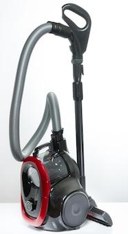 Aspirapolvere nero e rosso con il contenitore senza tubi flessibili su un bianco
