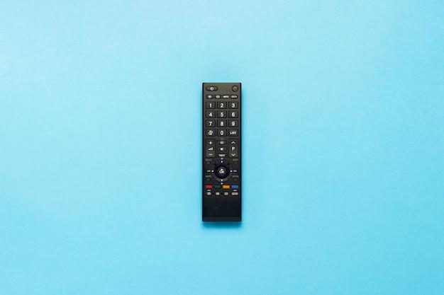 Telecomando nero su sfondo blu. il concetto di televisione, film, programmi tv, sport. vista piana, vista dall'alto.