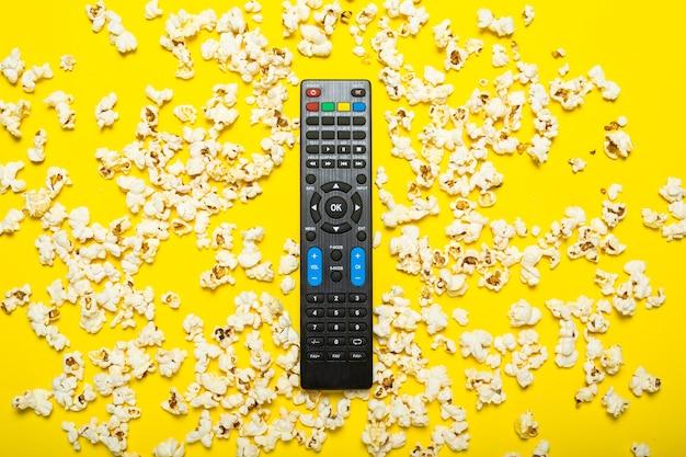 Telecomando nero da tv, sintonizzatore tv o sistema audio su giallo con popcorn