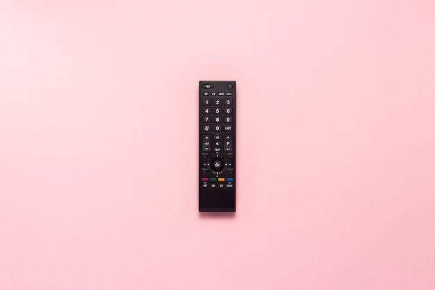 Telecomando nero su uno sfondo rosa. il concetto di televisione, film, programmi tv, sport. vista piana, vista dall'alto.