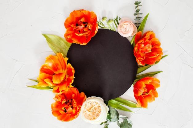 Carta rotonda nera con bellissimi fiori, foglie e copia spazio. auguri per le feste