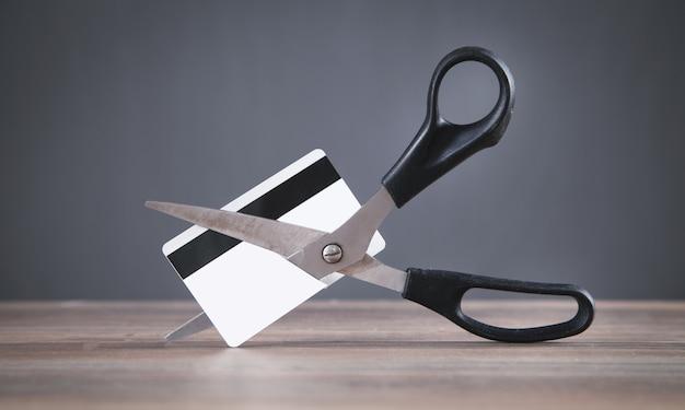 Forbici nere che tagliano una carta di credito.