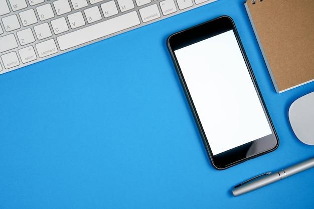 Spazio in bianco dello smartphone dello schermo nero e tastiera con il blocco note disposto su fondo blu. adatto per la grafica utilizzata per la pubblicità.