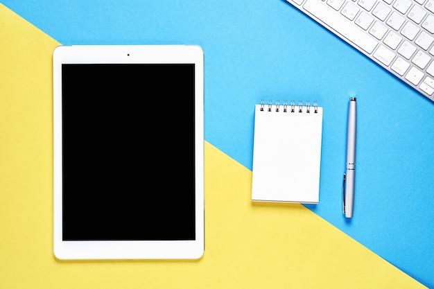 Spazio in bianco e taccuino della compressa dello schermo nero disposti su fondo giallo e blu pastello. adatto per la grafica utilizzata per la pubblicità.