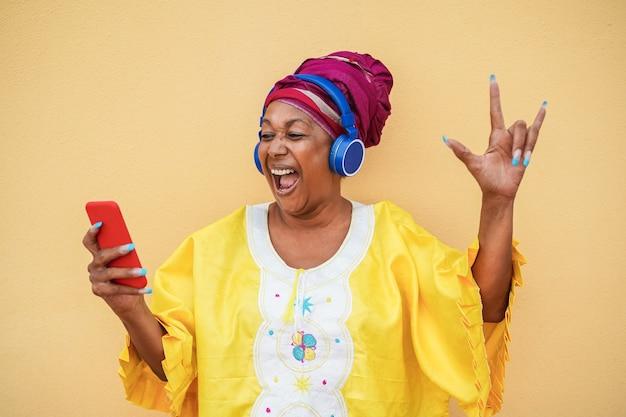 Donna maggiore nera nel vestito africano tradizionale che balla alla musica rock con il telefono cellulare - focus sul viso