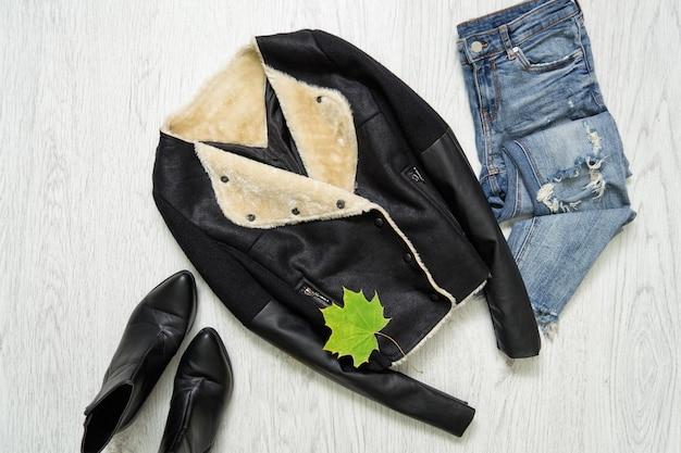 Cappotto di montone nero, stivali, jeans e foglie d'acero. concetto alla moda