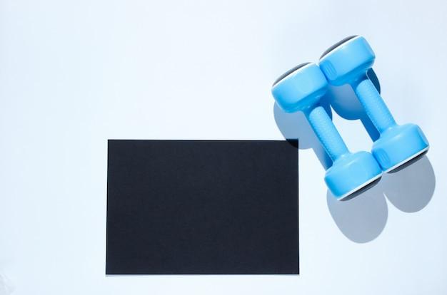 Foglio di carta nero per lo spazio della copia, manubri di plastica su un tavolo grigio. tavolo fitness creativo