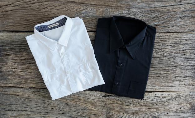 Camicia nera e camicia bianca su fondo di legno