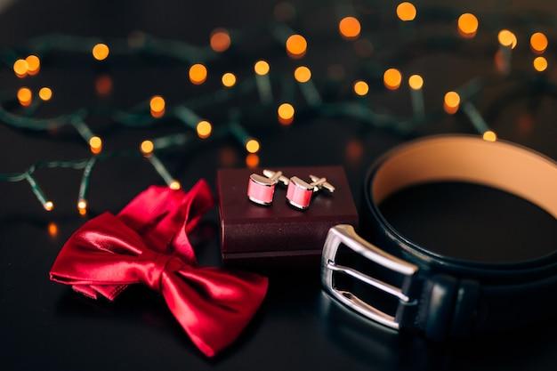 Scarpe nere dello sposo, papillon rosso, gemelli, cintura, su sfondo nero con bokeh luminoso. accessori per lo sposo da sposa.
