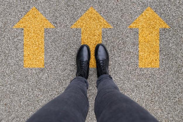 Scarpe nere in piedi sul pavimento di cemento asfaltato con il simbolo di tre frecce di direzione gialle. andando avanti, nuovo inizio e successo.. scarpe da piedi che camminano all'aperto. giovani selphie modern hipster