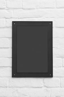 Targa nera o cornice per foto con spazio vuoto per il tuo design su uno sfondo di muro di mattoni.
