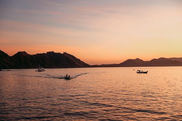 Siluetta nera delle colline con la tradizionale barca a vela sul mare a labuan bajo