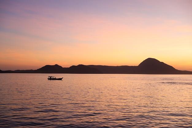 Siluetta nera delle colline con la barca da pesca tradizionale che naviga sul mare a labuan bajo
